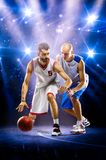 Two basketball players in spotlights. Two basketball players in action in gym in lights Royalty Free Stock Images