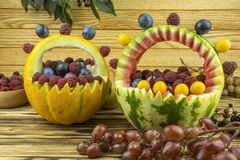 Two baskets of watermelon and cantaloupe, are one the among the. Grape, raspberries, blackberries, lie on a wooden table next to baskets of watermelon and melon Stock Photo