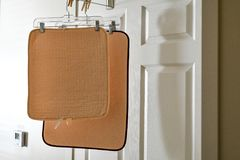 Two bath rugs being hung on the bathroom door to dry out from a recently taken shower. royalty free stock photos