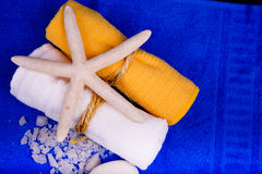 Two bath towels with starfish and sea salt on blue Royalty Free Stock Images