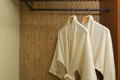 Two bathrobes hanging in warmly design closet Stock Photos