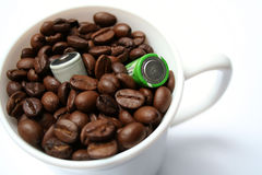 Two batteries and cup with grains of coffee. Two batteries in a cup with grains of coffee Royalty Free Stock Images
