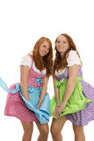 Two bavarian dressed girls fighting with wind. On white background Royalty Free Stock Photography