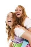 Two bavarian dressed girls having fun. On white background Royalty Free Stock Image