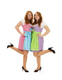 Two bavarian dressed girls lifting their feet. On white background stock photo