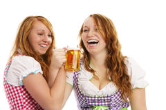 Two bavarian girls cheering with beer. On white background Royalty Free Stock Photography