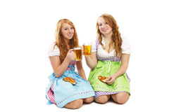 Two bavarian girls with pretzels and beer kneeling. On floor on white background Stock Images