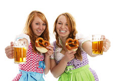 Two bavarian girls with pretzels cheering with bee. R on white background Royalty Free Stock Photography