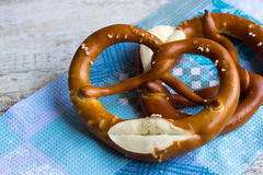 Two Bavarian pretzels on a towel. Crispy Bavarian pretzels with salt on a blue towel Stock Images