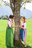Two bavarian women cling to a tree and smile at each other. Two bavarian women adhere to a tree in a meadow in the mountains and smile at each other. Both in Royalty Free Stock Photography