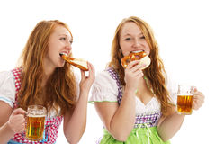Two bavarian women eating pretzels and holding bee. R on white background Royalty Free Stock Photography