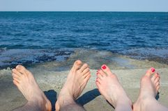 Two on a beach. Feet of the guy and the girl on a sea beach Royalty Free Stock Photography