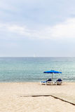 Two beach armchairs and umbrella Stock Image