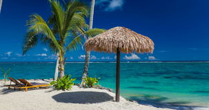 Two beach chair under umbrella with palm trees, Samoa stock video