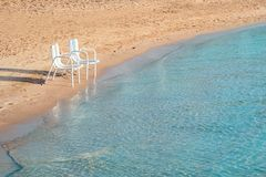 Two Beach Chairs. Two empty beach chairs on a lonely quite beach early in the morning. The location is at Hurghada, Egypt Stock Images