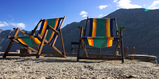 Two beach chairs. On stone pier with sky in background, Boka Kotorska bay, Montenegro Royalty Free Stock Photos