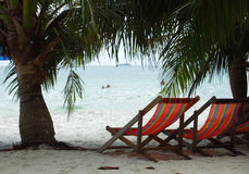 Two beach chairs on  beach under palm-trees near the sea Stock Image