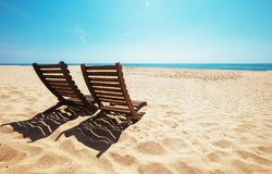 Two beach chairs on empty ocean beach under bright shining sun Stock Photo