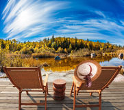 Two beach chairs and hat on the riverbank. Lovely place to relax. Cirrus clouds are reflected in the Winnipeg River. Old Pinawa Dam Park. The concept of Royalty Free Stock Photo