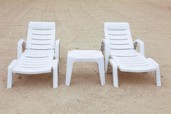 Two beach chairs. And plastic small table on sand Stock Photo