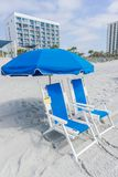 Two beach chairs for rent. Two beach chairs and an umbrella on the beach for rent Stock Photos