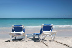 Two Beach Chairs on Sand Beach and Ocean. Two beach chairs on a beautiful Caribbean tropical beach in Dominican Republic  with white sand and green ocean Stock Image