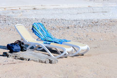 Two Beach Chairs. On sandy beach with blue towel and backpack Stock Photos