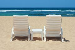 Two beach chairs on shore Stock Photo