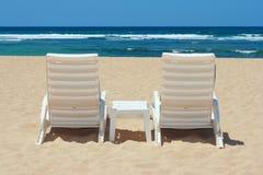 Two beach chairs on shore. Two sun beach chairs on beach sand near ocean Stock Photo