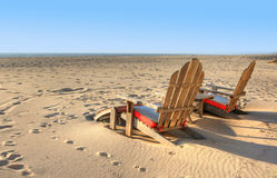 Two beach chairs sitting in the sand. On a sunny day Stock Images