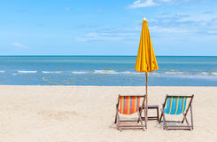 Two beach chairs with sun umbrella on beautiful beach. Concept for rest, relaxation and holiday Royalty Free Stock Image