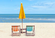 Two beach chairs with sun umbrella on beautiful beach. Royalty Free Stock Image