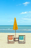 Two beach chairs with sun umbrella on beautiful beach. Stock Photo