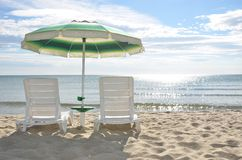 Two beach chairs and a sun umbrella. On the beach sand near the sea in sunny day Royalty Free Stock Images