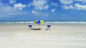 TWO BEACH CHAIRS AND SUN UMBRELLA ON A SANDY BEACH Stock Photo
