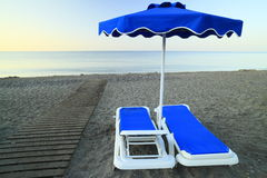 Two beach chairs. With sunshade on the beach Royalty Free Stock Photo