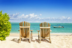 Two beach chairs on tropical shore, horisontal composition Royalty Free Stock Photography
