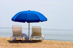 Two beach chairs and umbrella. Two empty beach chairs on the beach overlooking the ocean, with towels and a blue umbrella royalty free stock photos
