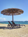 Two beach chairs with umbrella on a beach. There are two beach chairs and umbrella on a beach. There is no people. It was taken in Šibenik, Croatia Royalty Free Stock Photo