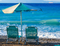 Two beach chairs and umbrella on shore of a pebbly beach Greece Rhodes royalty free stock photo