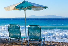 Two beach chairs and umbrella on shore of pebbly beach Greece Rhodes royalty free stock images