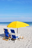 Two beach chairs and umbrellas on the beach Royalty Free Stock Images