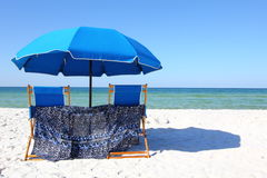 Two beach chairs under a blue umbrella on a white sandy beach Stock Photo