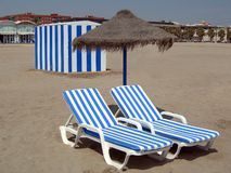 Two beach chairs under umbrella and a cabin Royalty Free Stock Photography