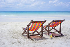 Two beach chairs on the white sand beach before blue sea Royalty Free Stock Photography
