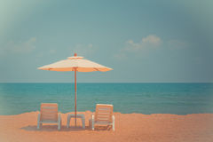 Two beach chairs and white umbrella on the tropical beach. At daytime. Vintage tone Stock Image