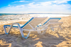 Two beach chaise lounges on the sand of beach. Sunset sunny time. Summer travel concept royalty free stock photo