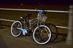 Beach Cruisers at Night. Two beach cruisers locked up on the boardwalk while their riders explore and probably grab a bite to eat Stock Image