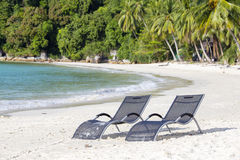 Two beach loungers on the beach next to the sea on a tropical Perhentian Islands, Malaysia. Two beach loungers on the sand beach and coconut palm trees next to stock photography