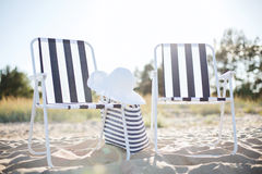 Two beach lounges with beach bag and white hat Royalty Free Stock Photography